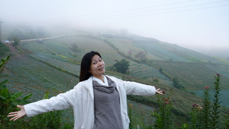 Portrait Of Smiling Young Woman Against Landscape During Foggy Weather