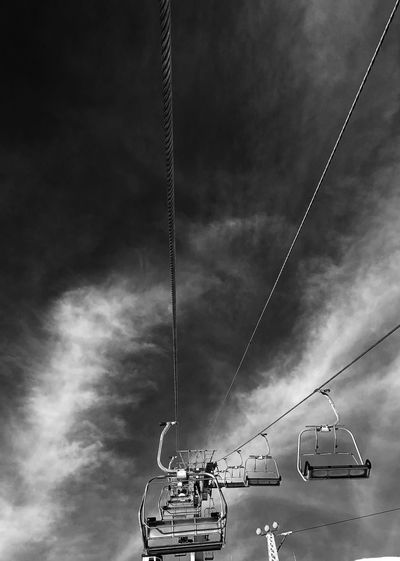 Low angle view of overhead cable cars against sky