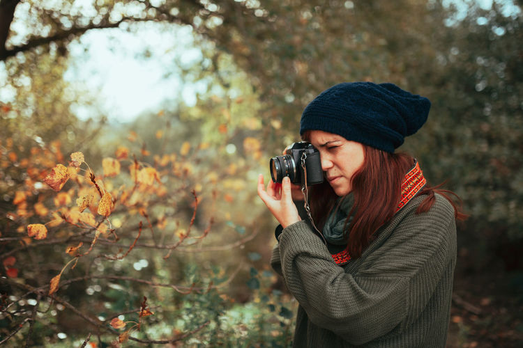 Young woman taking photos in the forest with an old analog camera