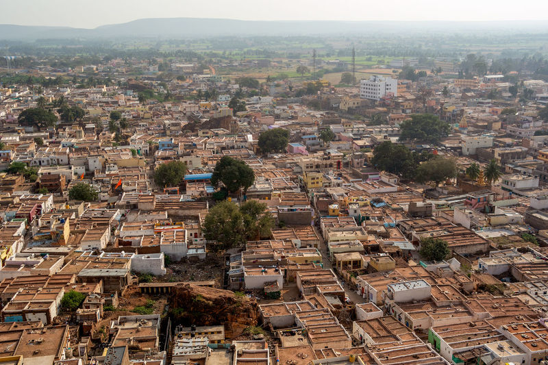 High above view of the flat roof houses and city scape of Badami, India. Building Exterior Architecture Built Structure City Residential District Cityscape Building Crowd Crowded High Angle View Day Community Outdoors Nature Tree Roof Town House Plant TOWNSCAPE Settlement Urban Sprawl Apartment Badami India