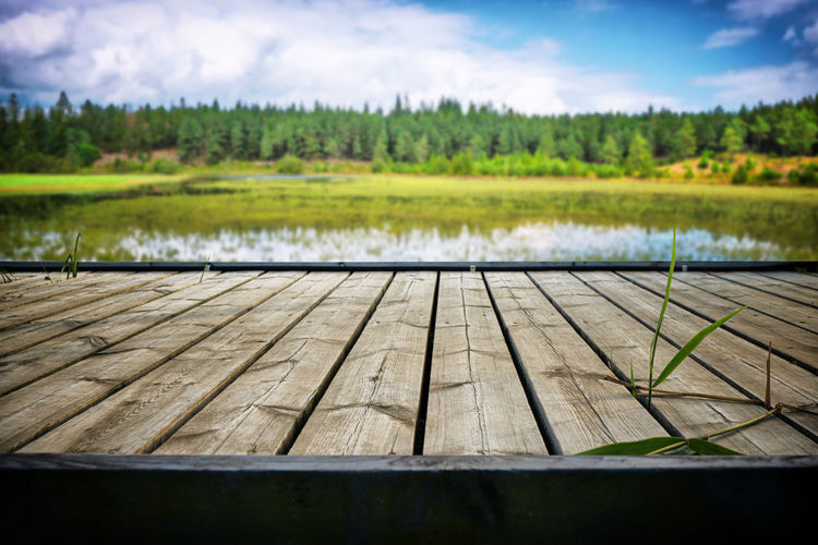 Close-up of wood by lake against sky
