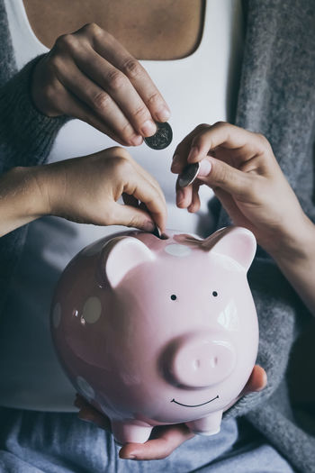 Close-up hands putting coin in happy smiling piggy bank. people saving money for household payments