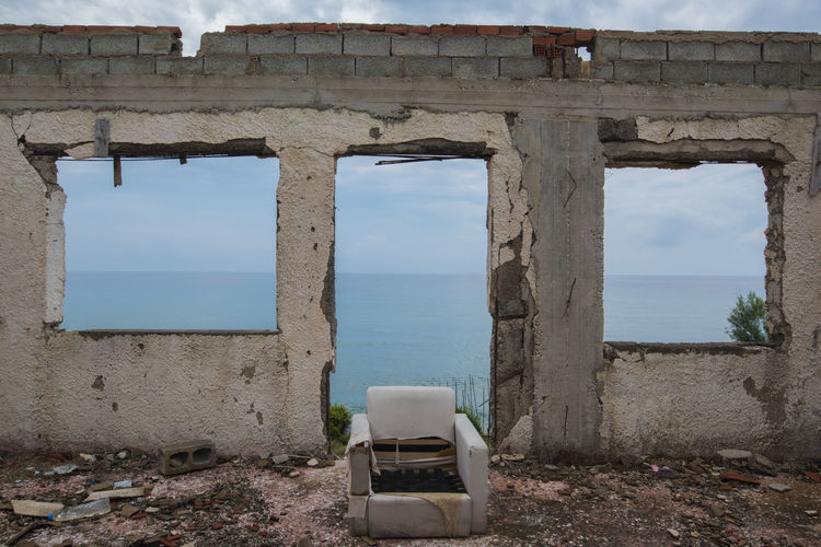 View of abandoned building by sea against sky