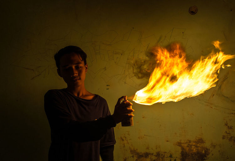 Man Spraying Fire With Aerosol Can Against Wall