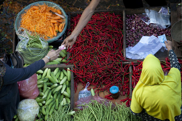 High Angle View Of Cropped Hands Exchanging Money Over Vegetables At Market Stall