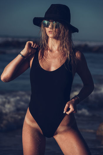 Woman wearing bodysuit and sunglasses standing against sea