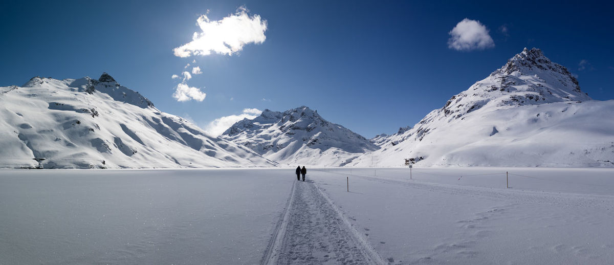 People walking on snow covered field against sky