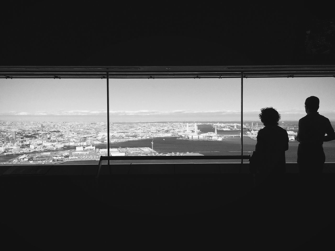 Two People Watching Cityscape Form High Floor Window