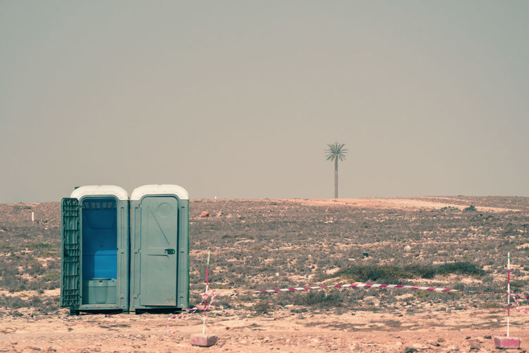 Portable toilet in dessert with palm against clear sky