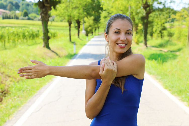 Woman stretching outdoors Arms Bergamo Hair Happy People Nature Stretching Legs Trees Beautiful Woman Blue Fitness Fitness Model Fitness Training Fitnessgirl Fitnessmodel Fitnessmotivation Italy Legs Smiling Face Street Stretching Stretching My Legs Tank Top Training Woman Hair Woman Portrait