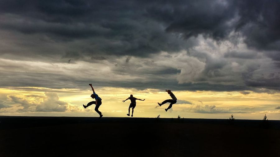 Silhouette people jumping on land against sky during sunset