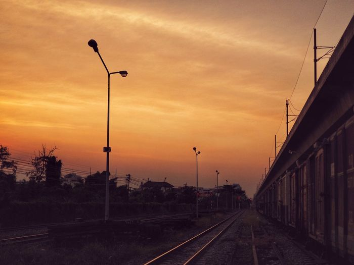 Street lights by railroad tracks against sky during sunset
