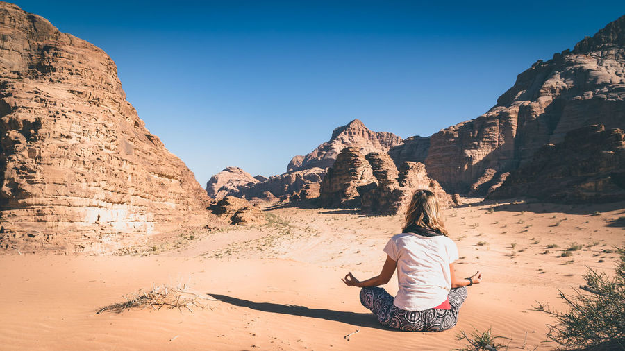Rear View Of Woman Meditating On Field At Desert