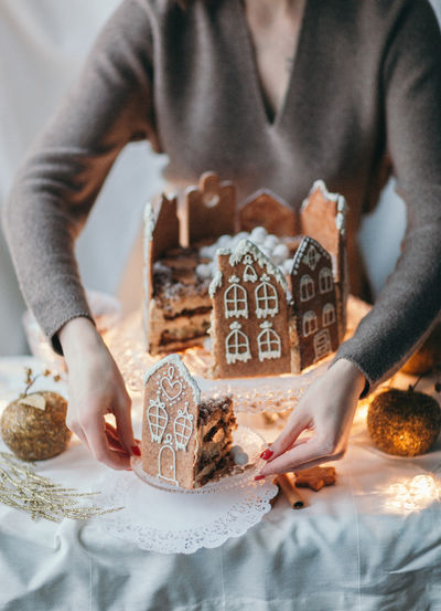 Food Indoors  Food And Drink Sweet Food Baked Real People Cookie Holding Women Table People Celebration Sweet Lifestyles Hand Gingerbread Cookie Temptation Piece Of Cake Serving Gingerbread Gingerbread House Homemade Cake Still Life