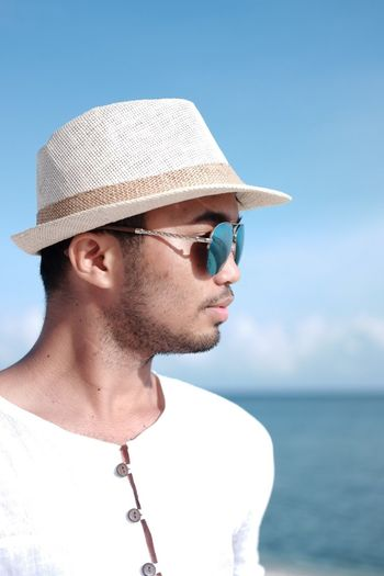 Young man wearing hat and sunglasses by sea