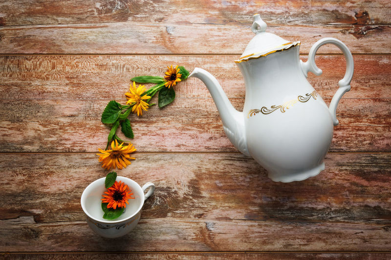 High Angle View Of Teapot And Flowers Arranged On Table