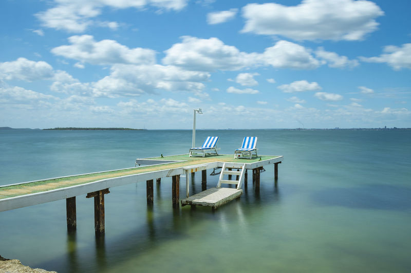 Lounge chairs on pier over sea against blue sky