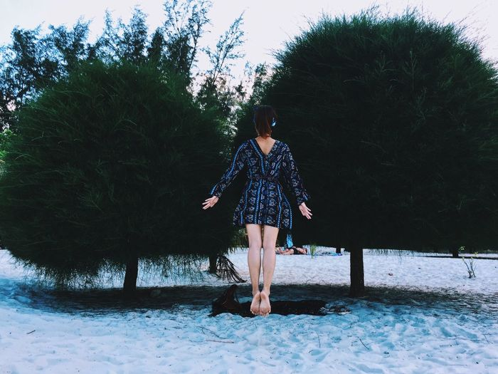 Rear view of woman levitating over sand against trees