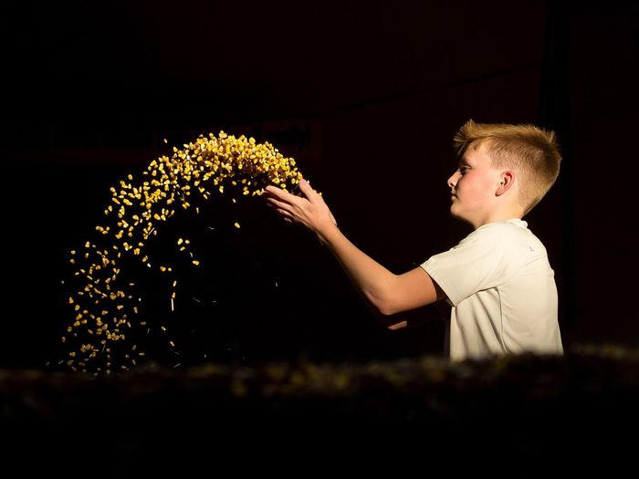 Boy throwing corn on field against sky at night