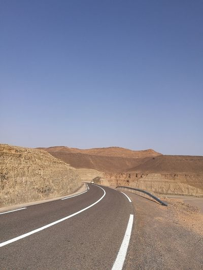 Empty Road On Desert Against Clear Blue Sky
