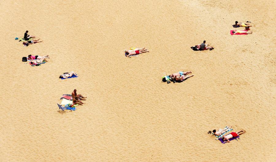 View of people sunbathing on shore