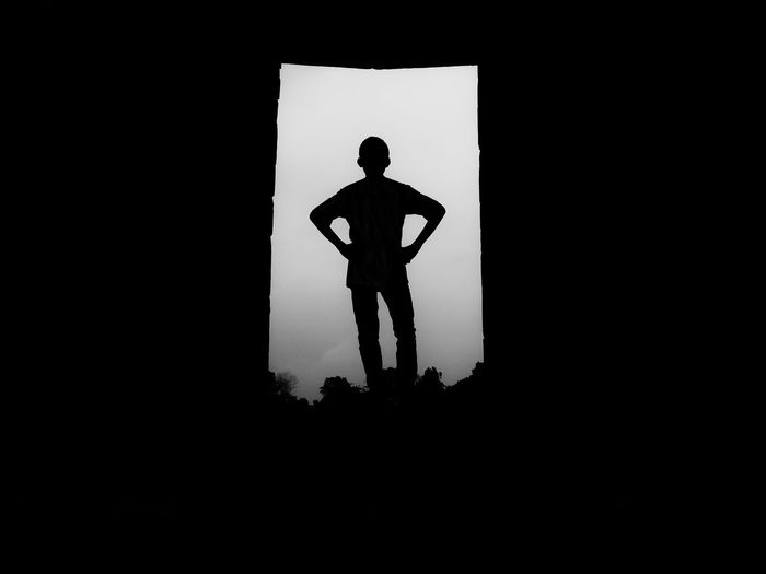 Rear view of silhouette man standing in doorway against sky