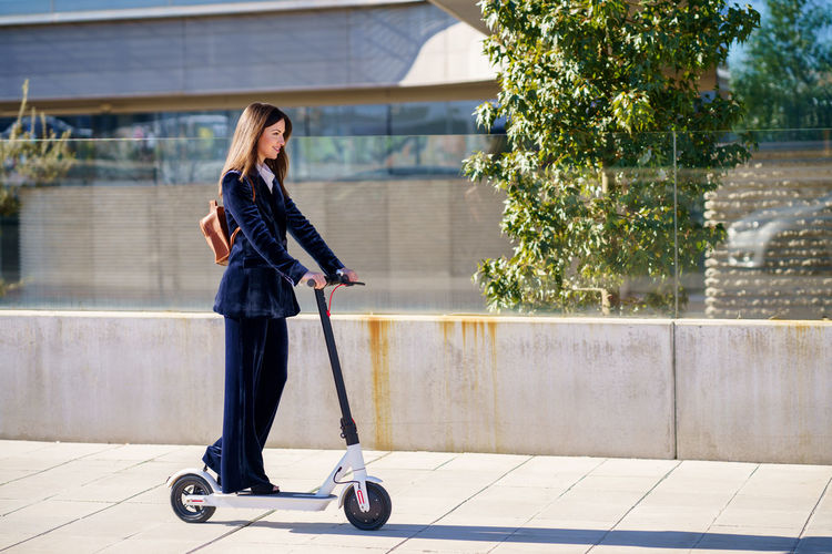 Woman riding electric push scooter on footpath in city