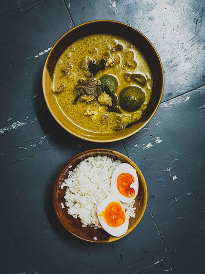 High angle view of green curry breakfast served on table