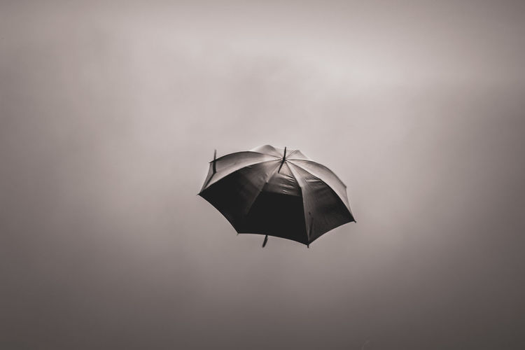Open umbrella flying in sky . black color umbrella flying in wind.