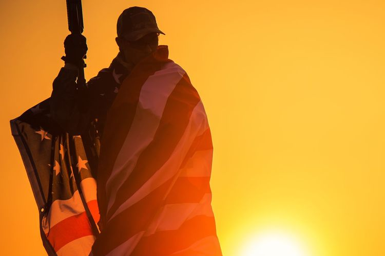 Soldier wrapped in american flag standing against sky during sunset