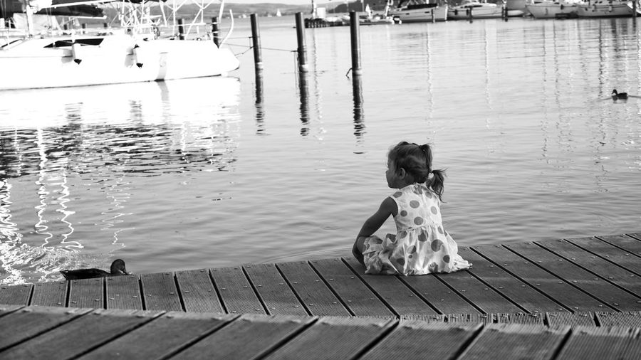 Rear view of girl sitting on pier over lake