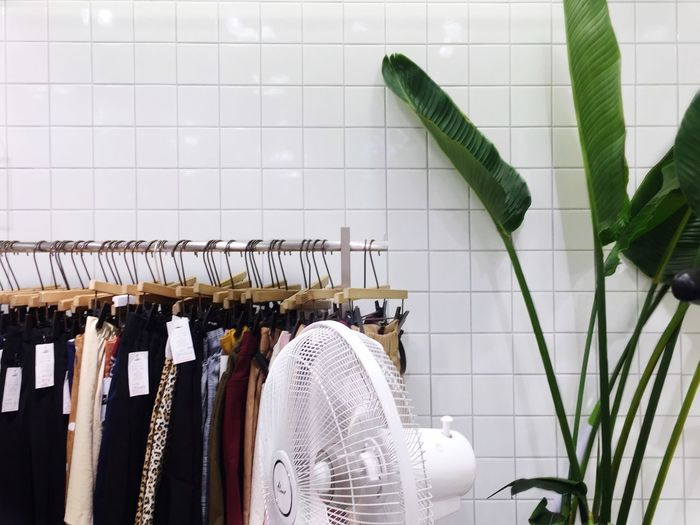 Electric fan against clothes hanging on rack in store