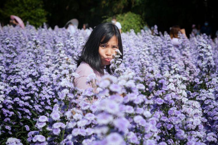 Portrait of girl on purple flowering plants