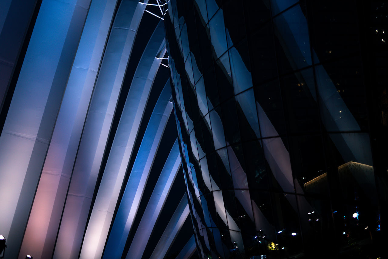 low angle view, built structure, architecture, night, building exterior, illuminated, modern, no people, pattern, building, glass - material, ceiling, blue, outdoors, city, reflection, lighting equipment, office building exterior, architectural column