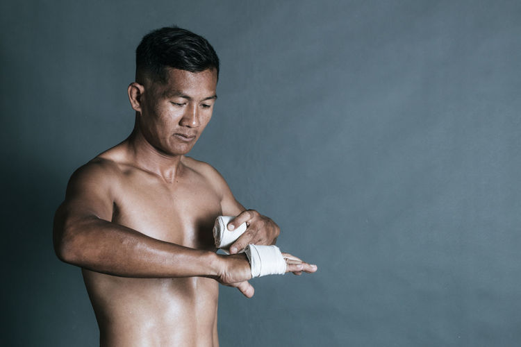 Shirtless man wrapping bandage on hand against wall