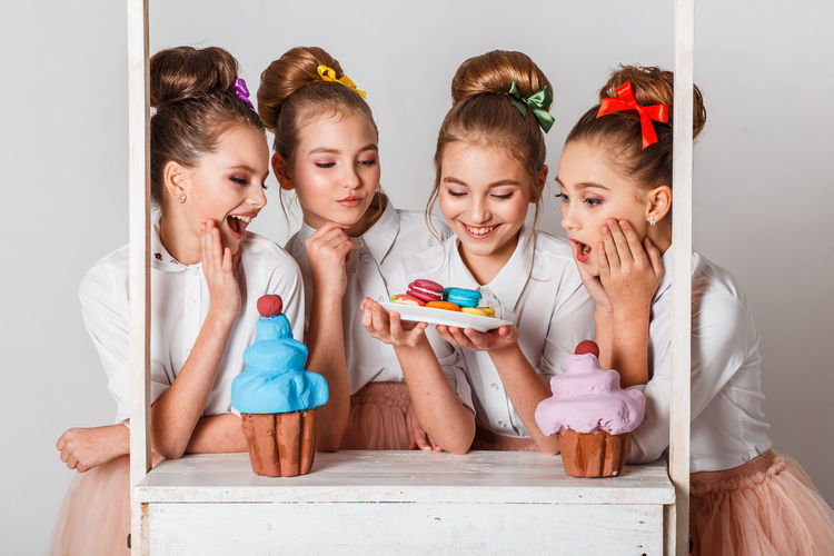 Girls having colorful macaroons against white background