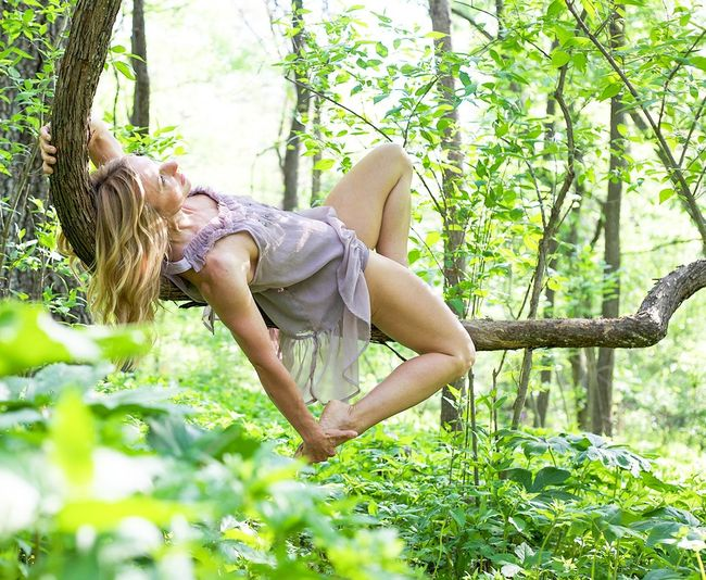 Woman performing yoga on tree