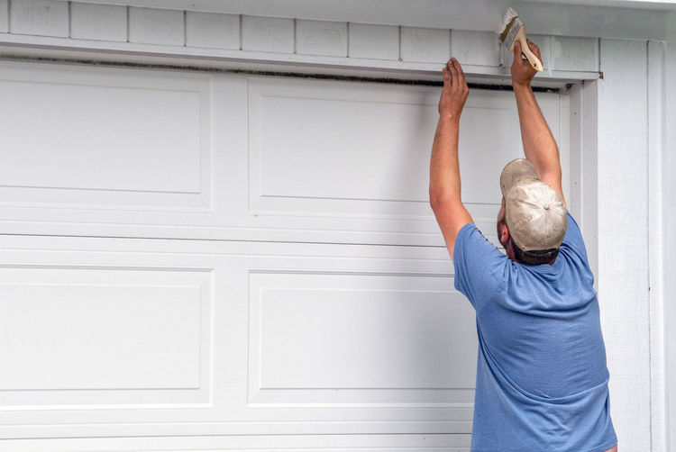 A worker paints trim around a garage , maintaining the structure for the future