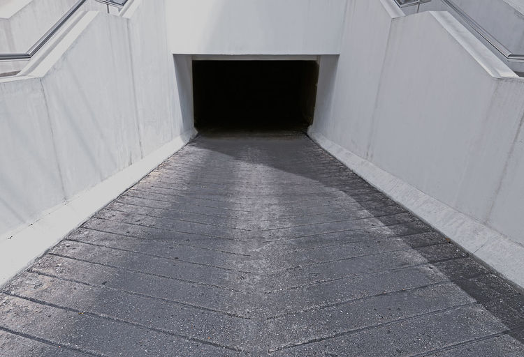 White walled underground car parking entrance to dark tunnel. Bangkok Subterranean Concrete Copyspace Downhill Entrance Garage Lines Parking Tunnel Underground White Architecture Flooring Door Built Structure No People Building Day Indoors  Wall - Building Feature Tile Empty City Tiled Floor High Angle View Open Abandoned Absence