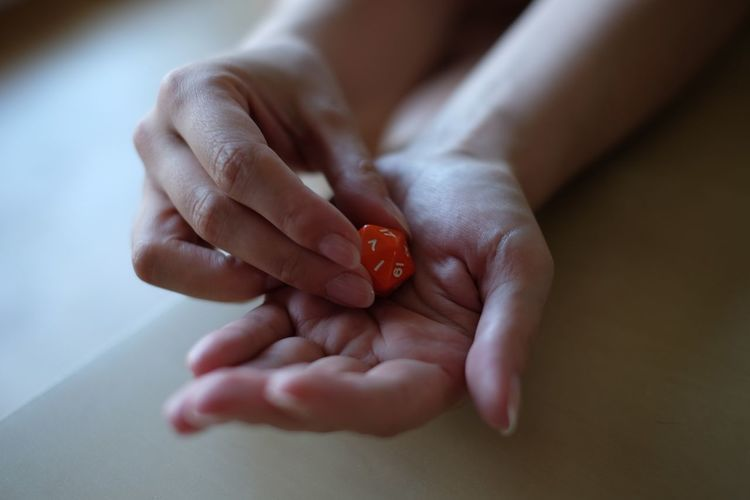Cropped Image Of Person Playing With Dice At Home