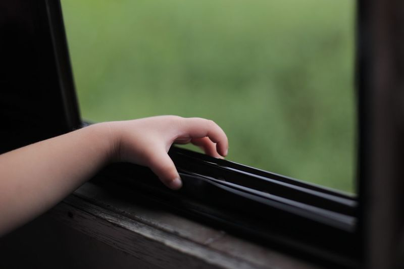 Cropped hand of child touching window