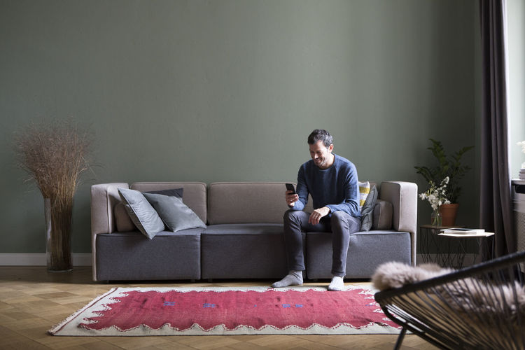 Full length of young man sitting on sofa at home