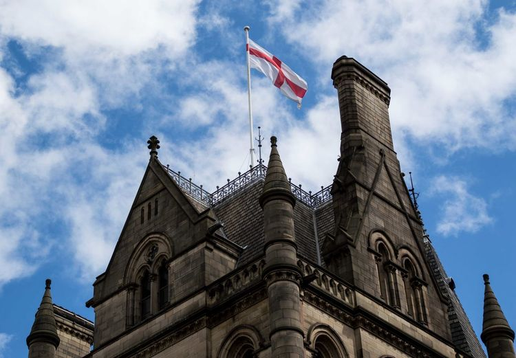 Low angle view of british flag on building against cloudy sky