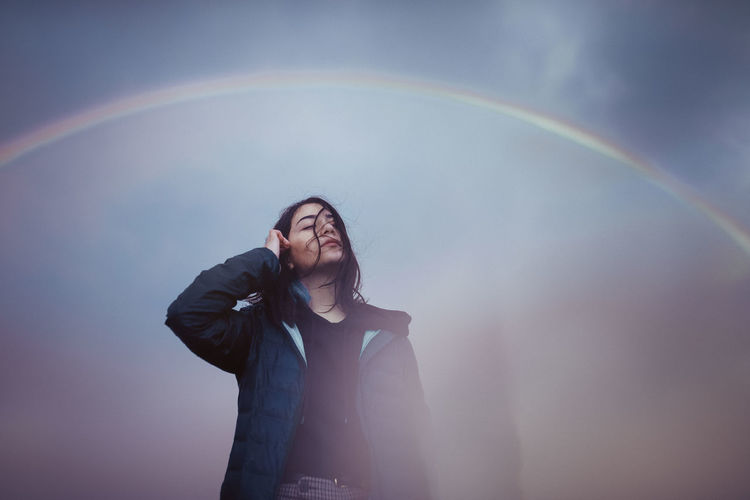 Full length of woman standing in rainbow