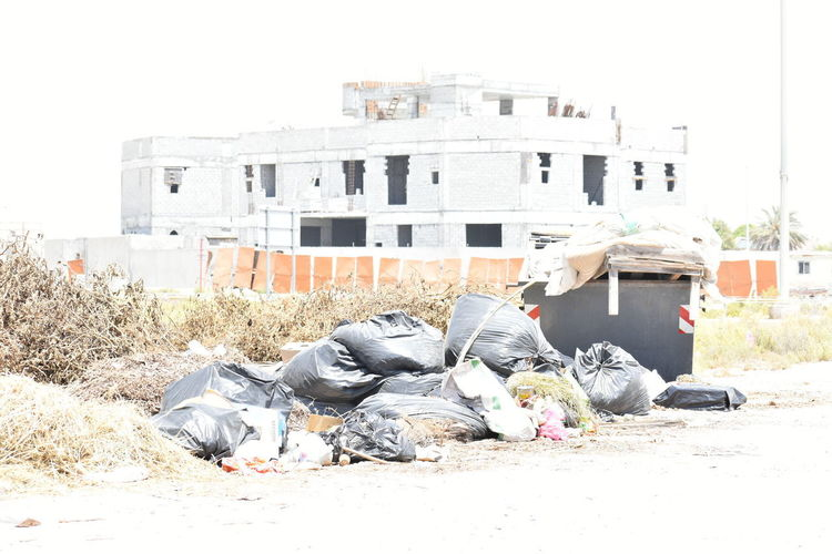 Garbage on street against buildings in city
