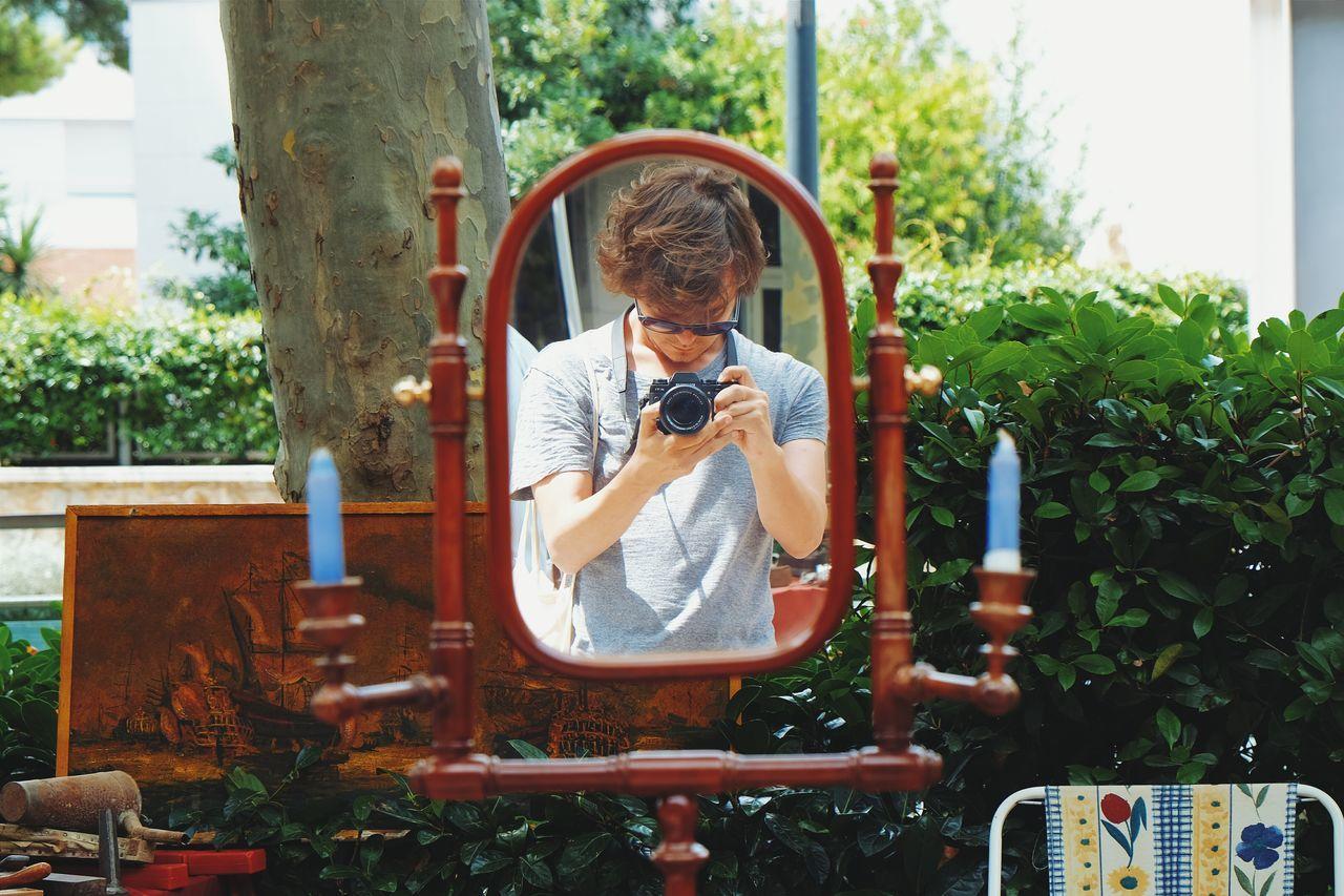 Man holding photo camera reflecting in mirror