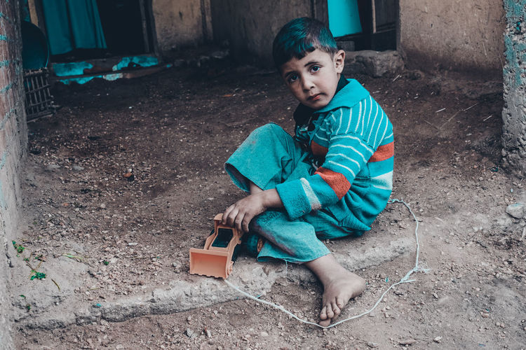 upper egypt The Fashion Photographer - 2018 EyeEm Awards The Portraitist - 2018 EyeEm Awards Boys Casual Clothing Child Childhood Cute Day Full Length Holding Innocence Leisure Activity Lifestyles Looking At Camera Males  Men One Person Real People Sitting Toy The Traveler - 2018 EyeEm Awards