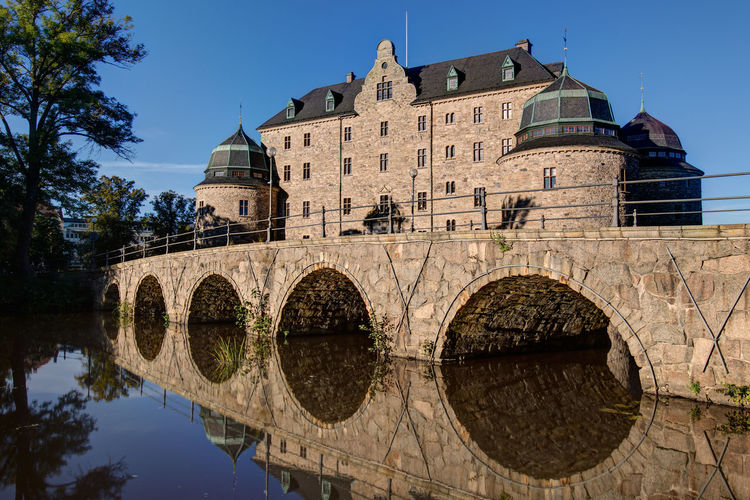 Orebro castle, Sweden. Medieval stone castle surrounded by a moat. 1300 Arch Arch Bridge Arched Architecture Blue Bridge Building Exterior Built Structure Castle Day Famous Place History No People Old Town Outdoors Reflection Sky Slott The Past Tranquility Travel Destinations Water Waterfront Örebro  First Eyeem Photo
