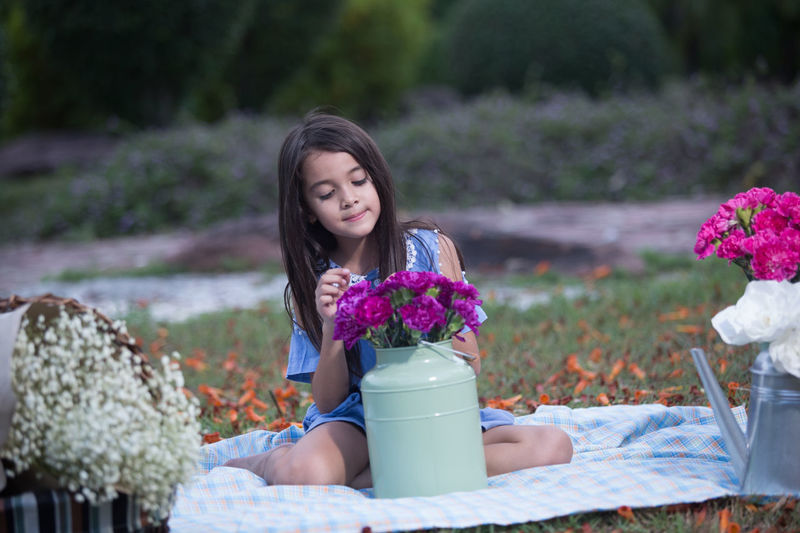 Cute Girl Arranging Flowers In Container While Sitting On Blanket In Park