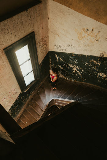 High angle view of woman sitting on staircase